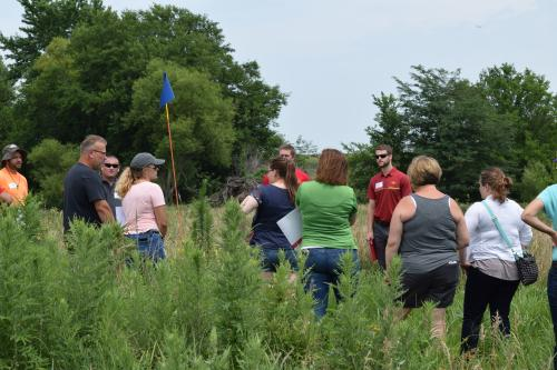 photo of field day attendees and Seth Appelgate at monarch habitat plot